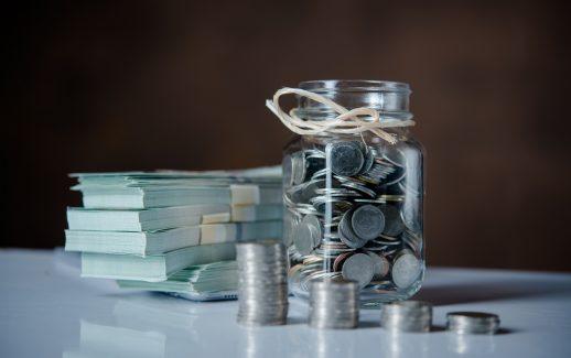 moedas-em-pote-cédulas-pilhas-de-moedas-em-mesa